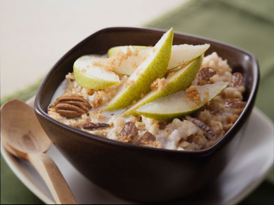 oatmeall topped with pears and walnuts in a bowl