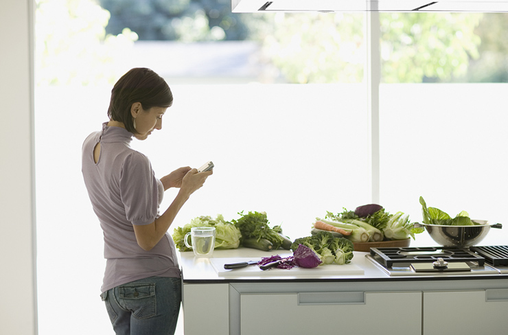 Woman Texting In Kitchen