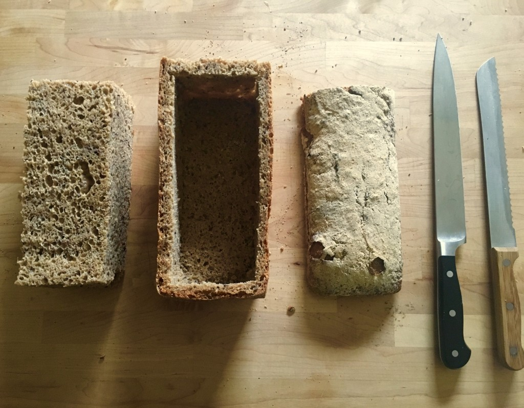 loaf of bread on a cutting board with the crust and top intact, but the middle removed in a block