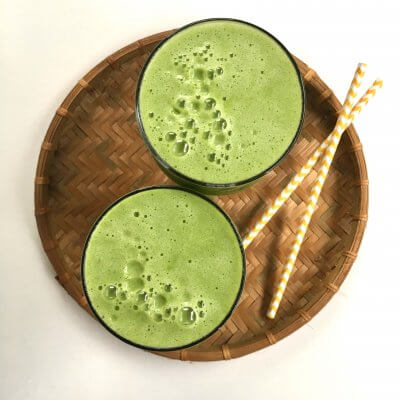 Green, frothy fresh pear juice in glasses on a bamboo mat with straws