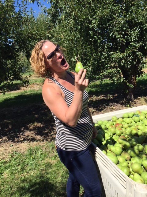 Woman with curly blonde hair in an orchard excitedly about to bite a fresh pear