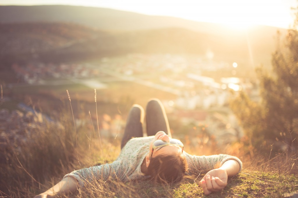 arefree happy woman lying on green grass meadow on top of mounta